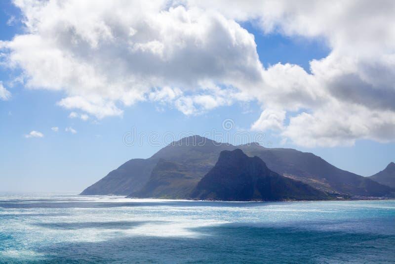 Meerblicktürkis-Ozeanwasser, blauer Himmel, weißes Wolkenpanorama, Mountain View Landschaft, Küstenreise Cape Towns, Südafrika lizenzfreie stockfotografie
