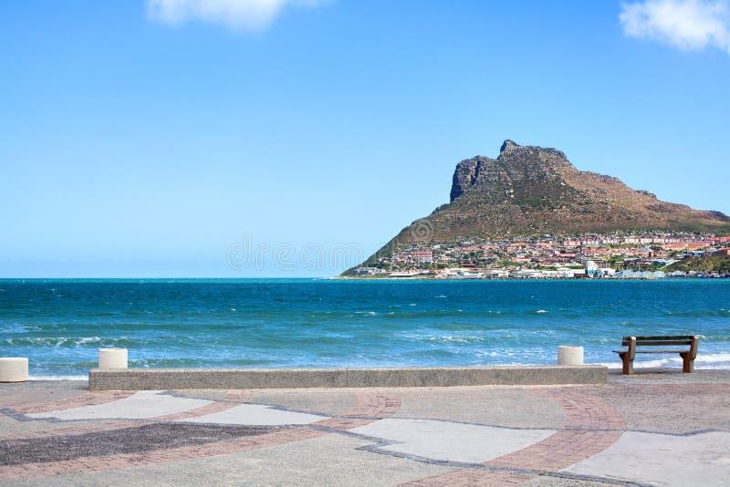 Meerblicktürkis-Ozeanwasser, Panorama des blauen Himmels, Damm mit leerer Bank, Küstenreise Cape Towns, Südafrika lizenzfreie stockfotos