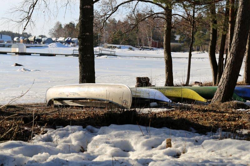 Meerdere kleurrijke Kayaks en Canoes geparkeerd op een strand in Espoo tijdens het voorjaar royalty-vrije stock afbeelding