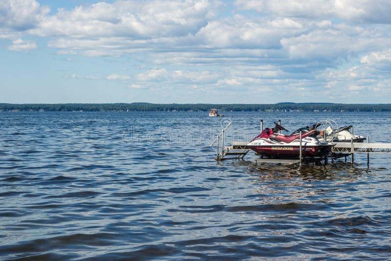 Meeres--doo Jet-Skis und -leute, die Spaß auf einem Boot auf Oneida Lake, NY-Zustand haben lizenzfreies stockbild