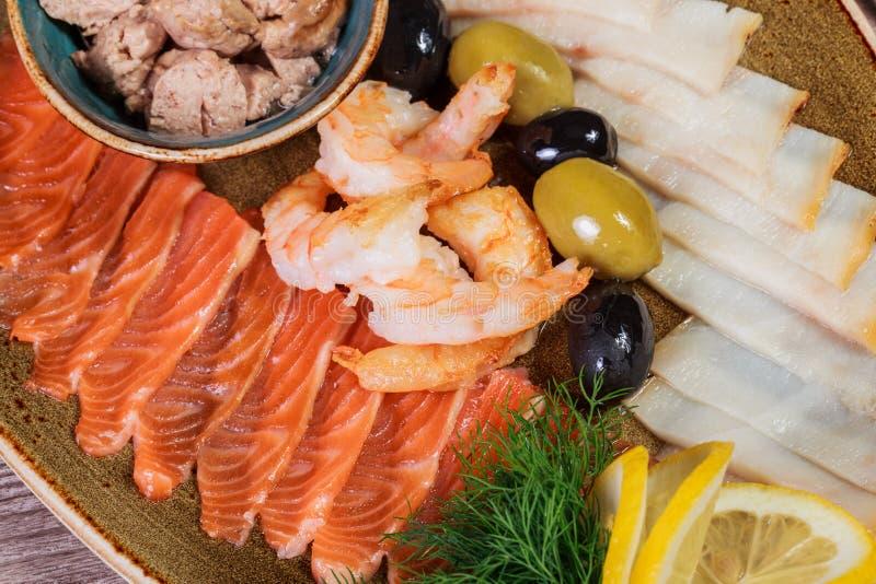 MEERESFRÜCHTE-SERVIERPLATTE Frische Dorschleber, Lachs, Garnele, ScheibenFischfilet, verziert mit Kraut, Zitrone und Oliven stockfotos