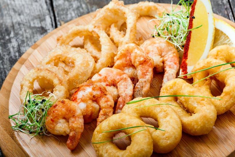 Meeresfrüchteservierplatte mit frittierten Kalmarringen, Garnele und den Zwiebelringen verziert mit Zitrone auf Schneidebrett auf stockfoto