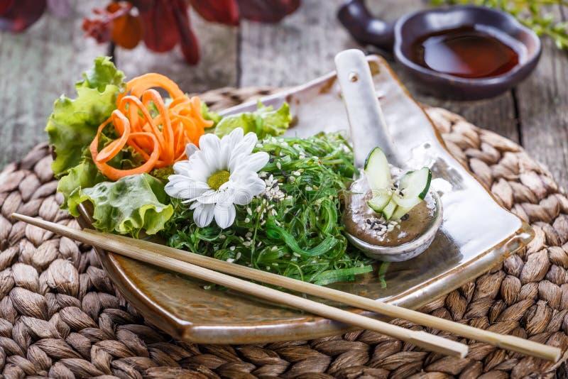 Meerespflanzen-Salat wakame in der Platte mit Essstäbchen auf Bambusmatte stockfotos