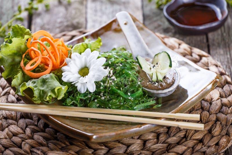 Meerespflanzen-Salat wakame in der Platte mit Essstäbchen auf Bambusmatte Japanische Küche - gesunde Meeresfrüchte lizenzfreies stockfoto