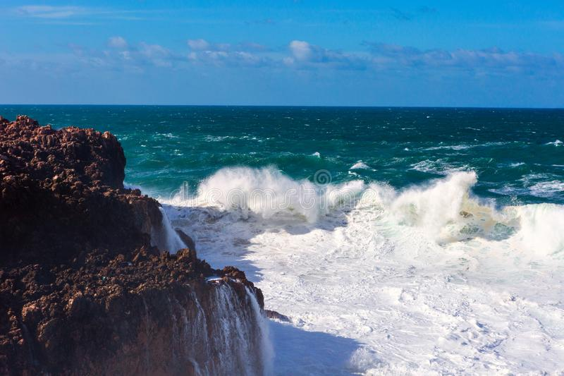 Meereswellen, die Felsenklippe am Praia DA Bordeira, Portugal schlagen stockfotografie