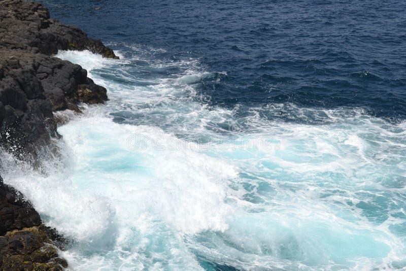 Meereswellen stoßen auf vulkanischen Felsen zusammen stockfotos