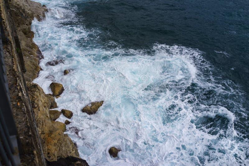 Meereswoge schlug die Klippe auf Felsenküste mit Spray und Schaum vorher stockbild