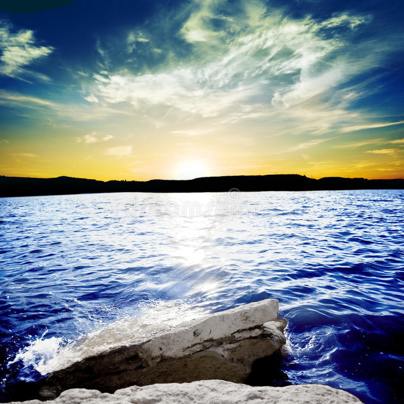 Meereswogen, die auf einem Felsen mit Sonnenuntergang brechen stockfotografie
