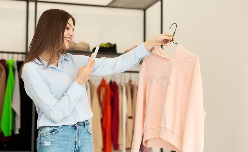 Meerjarig meisje met foto van een kledingstuk in een kledingwinkel stock foto's