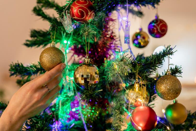 Meerjarige vrouw die thuis kerstboom versiert stock foto