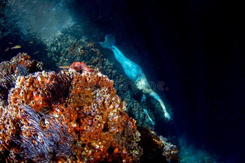 Meerjungfrau, die unter Wasser im tiefen blauen Meer schwimmt stockbild