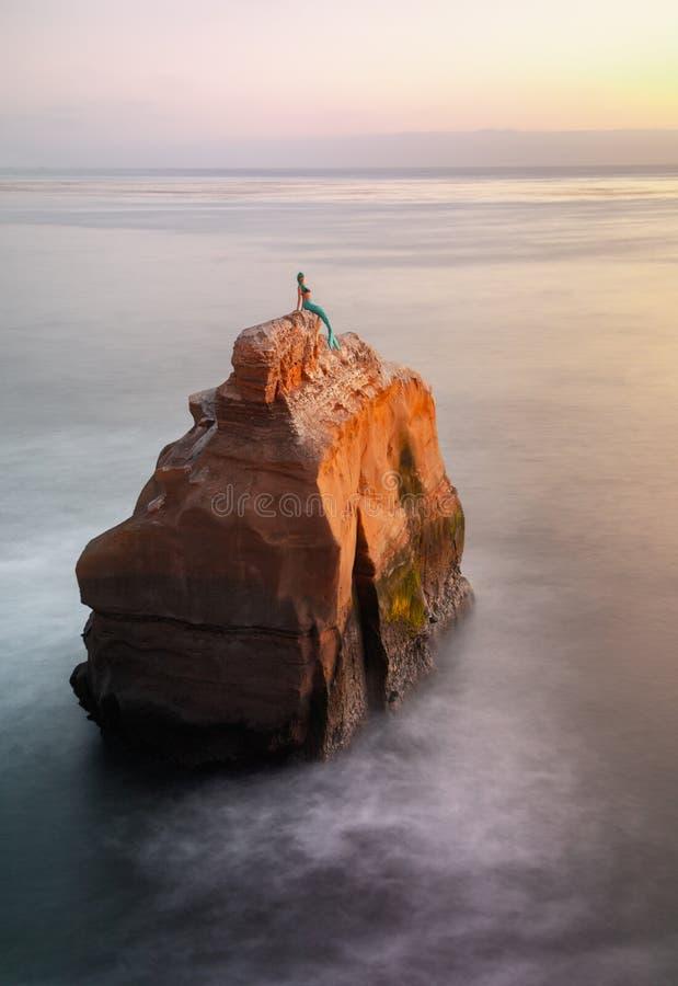 Meerjungfrau-Mannequin, das auf Ozean-Felsen während der Sonnenuntergang-langen Ausstellungen sitzt lizenzfreie stockbilder