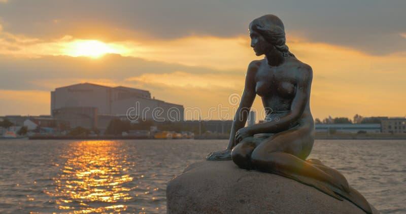 Meerjungfraustatue auf dem Stein im Meer bei Sonnenuntergang stockbilder