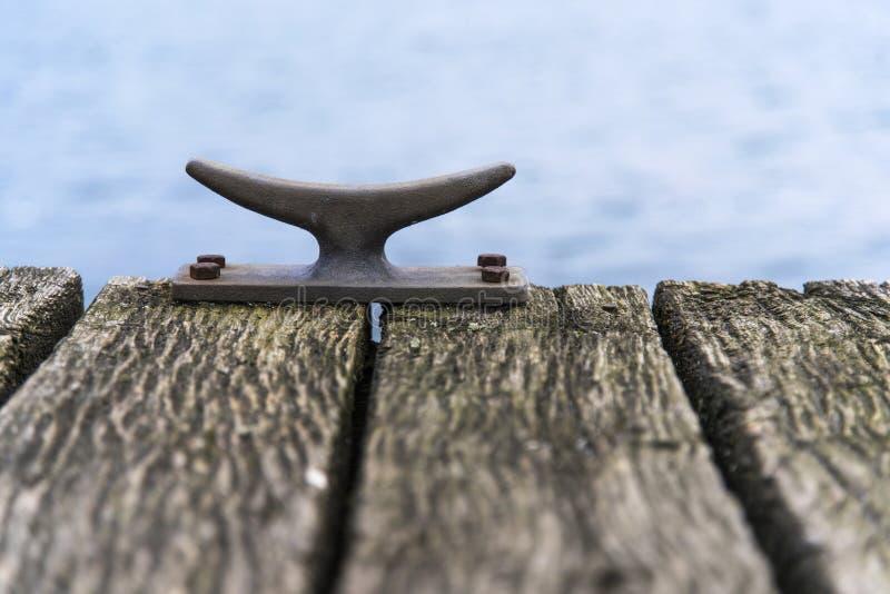 Meertrosmeerpaal van metaal op een houten pijlerbrug bij het overzees, cop royalty-vrije stock foto's
