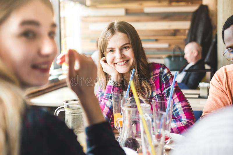 Meet young attractive people in the cafe. Friends chat, have fun, drink cocktails and eat.  stock photos