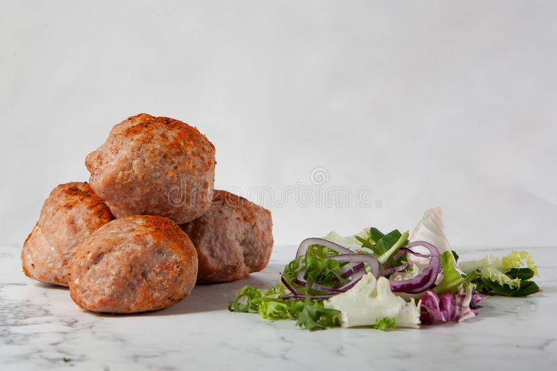 Meetballs lettuce white marble table. Meet balls and a salad with lettuce and onion on a white marble table stock photos