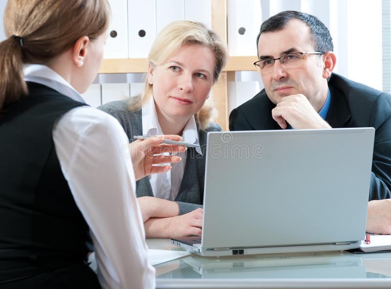 Meeting. Mid-adult couple meeting with financial planner stock image