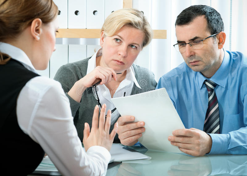 Meeting. Mid-adult couple meeting with financial planner royalty free stock image