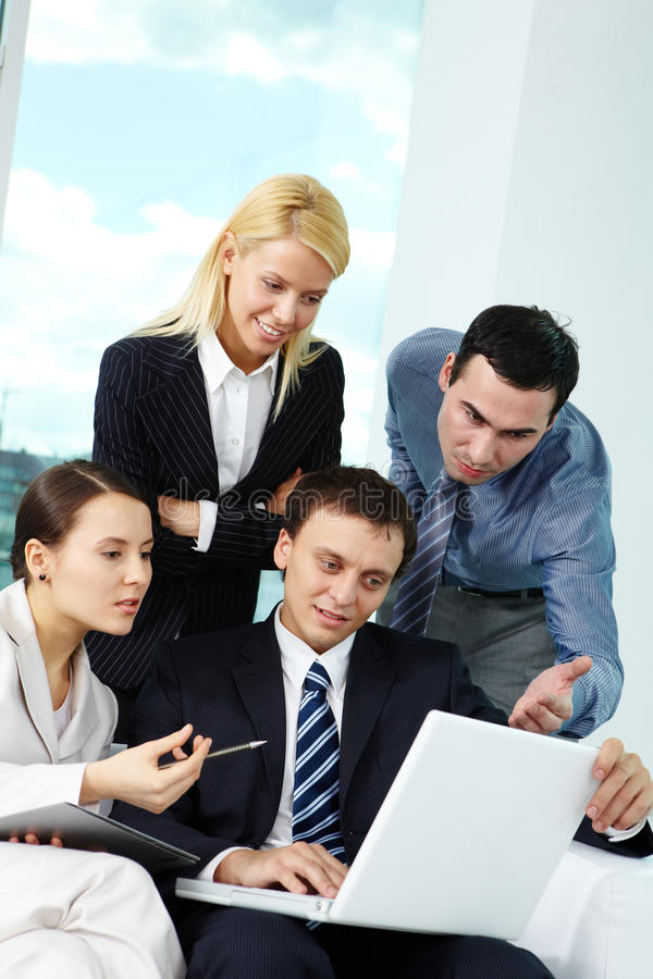 At meeting. Portrait of several colleagues looking at laptop screen in office royalty free stock image