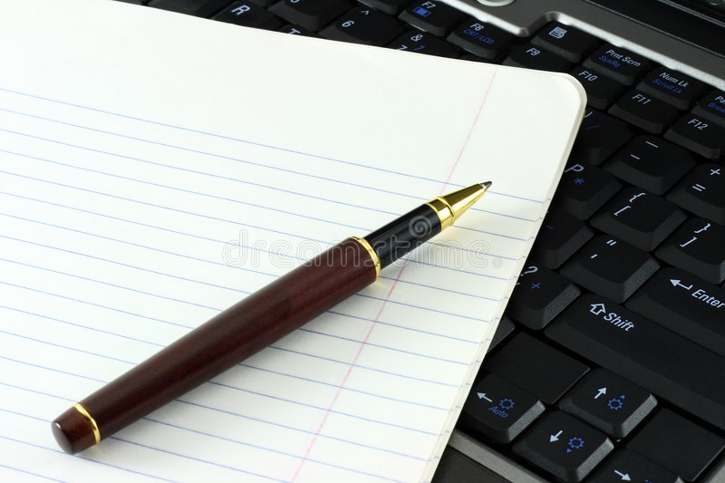 Notebook and pen on computer. A notebook and a ball point pen on top of a laptop computer