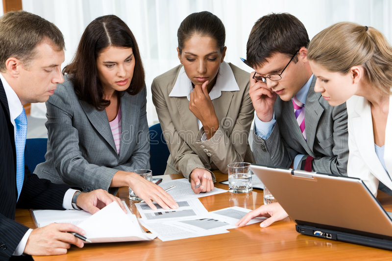 At meeting. Portrait of confident people looking seriously at business papers during working meeting