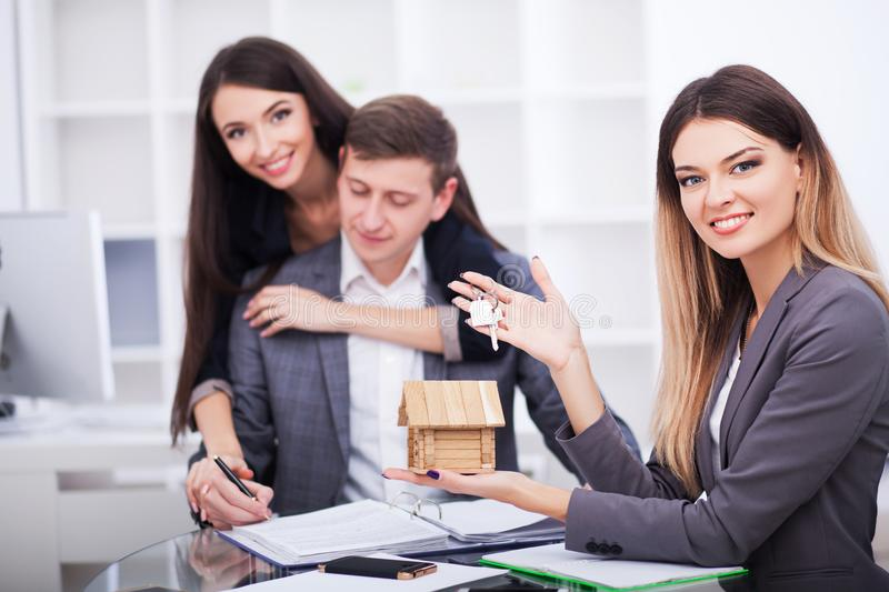Meeting with agent in office, buying renting apartment or house, buyers of real estate ready to conclude a deal, family couple sh. Aking hands with realtor after stock photos