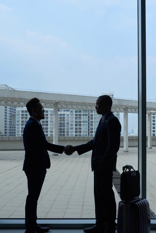 Meeting in airport. Vietnamese businessman meeting coworker in international airport stock image
