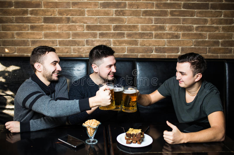 Meeting with the best friends. Three happy young men in casual wear talking and drinking beer while sitting in bar together stock photography