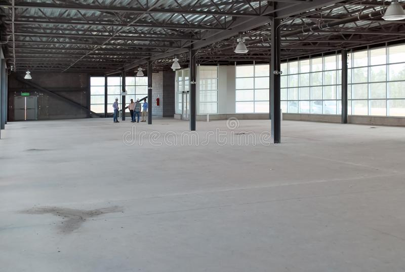 Meeting of group of builders and architects in empty warehouse. stock photo
