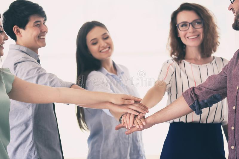 Meeting of business team putting hands together as symbol of unity royalty free stock image