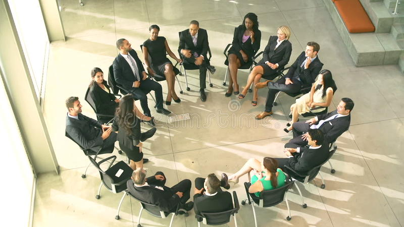 Meeting With Businesspeople Sitting In Circle On Chairs