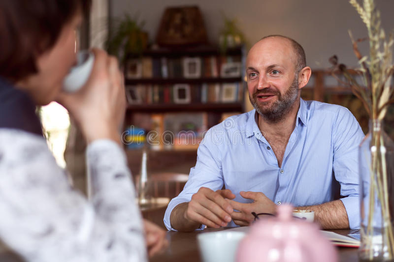 Meeting at the cafe. A handsome men in a shirt enthusiastically tells his girlfriend something and drinks tea royalty free stock photo