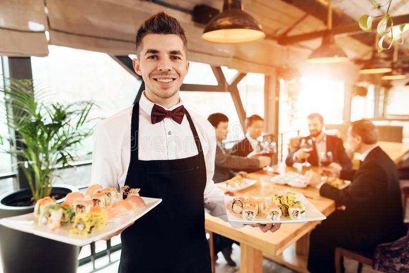 Meeting with chinese businessmen in restaurant. Waiter is posing with sushi. Meeting with chinese businessmen in suits in restaurant. Waiter is posing with stock image