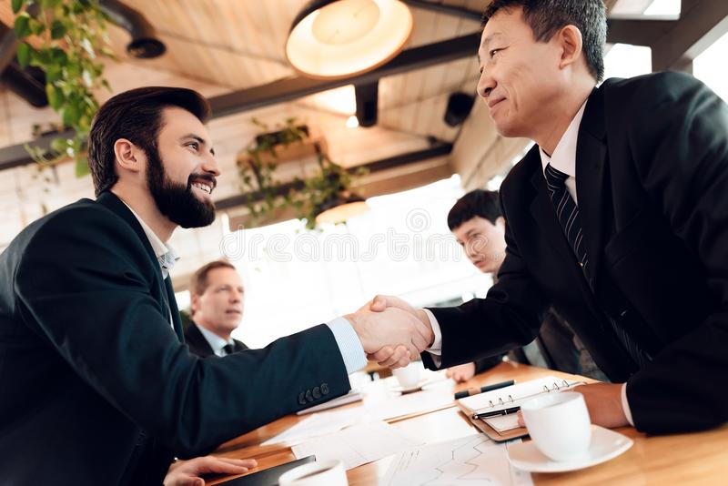 Meeting with chinese businessmen in restaurant. Men are shaking hands. royalty free stock photo
