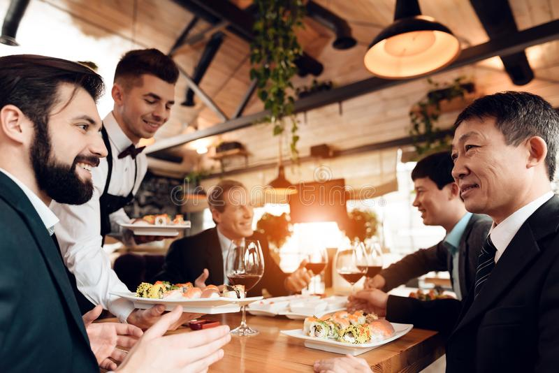 Meeting with chinese businessmen in restaurant. Waiter is bringing sushi. Meeting with chinese businessmen in suits in restaurant. Waiter is bringing sushi stock images