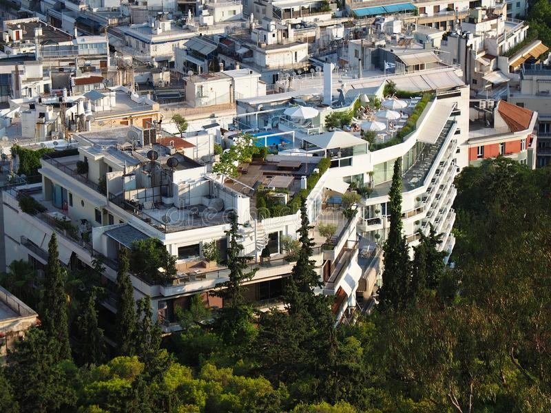 Meeting of City and Nature. City and nature meet in Athens, Greece, with natural forest next to urban buildings with rooftops and balconies with gardens, trees