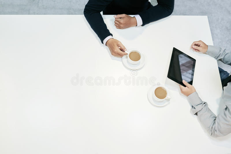 Meeting with coffee. Business colleagues drinking coffee during meeting in cafe stock photography