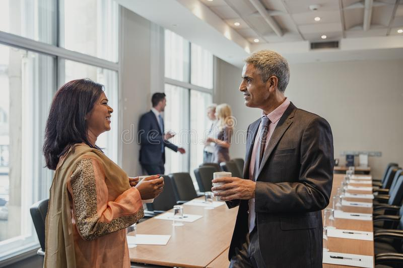 Meeting at the Conference. Business men and business women talking before the meeting starts. Being friendly and talking, getting to know each other royalty free stock photography