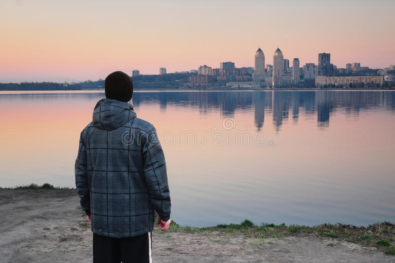 Meeting the dawn on the river bank. The guy meets the dawn standing on the river bank and looking away into the city stock image