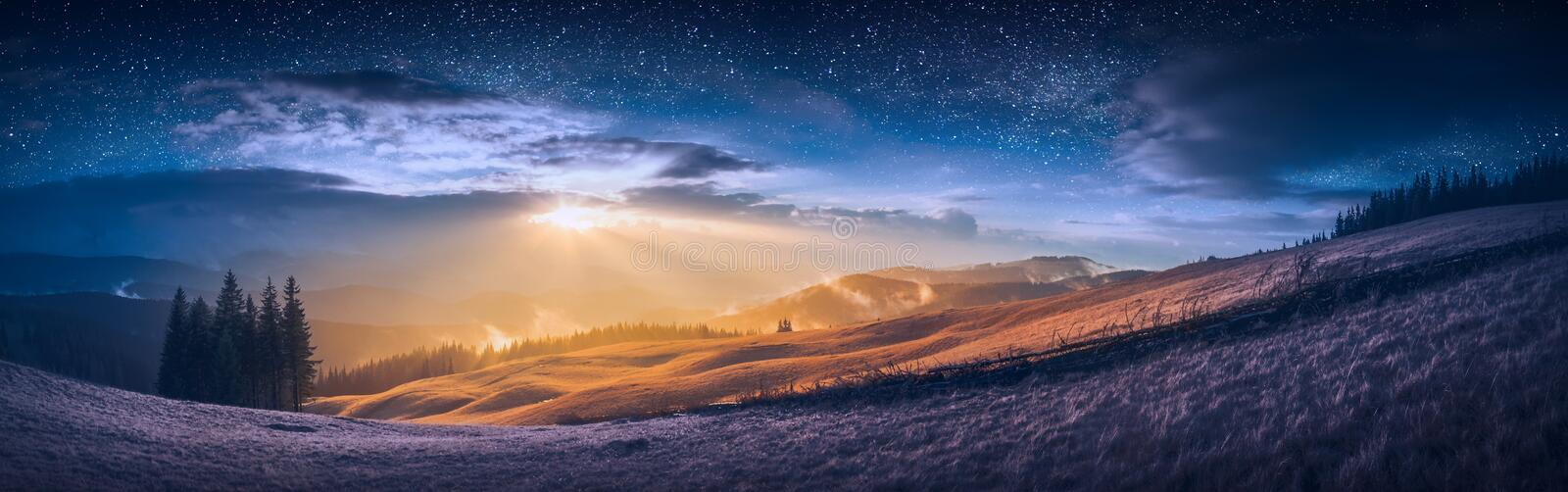 The meeting of day and night in a mountain valley. With wonderful gold light on a hills and bright stars in a sky stock photography