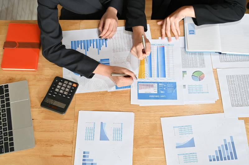 Meeting of financial, Two business working with finance paper and calculator with top view stock photo
