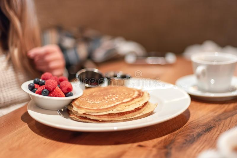 Meeting a friend for casual breakfast. Pancakes and fresh berries on table royalty free stock photo