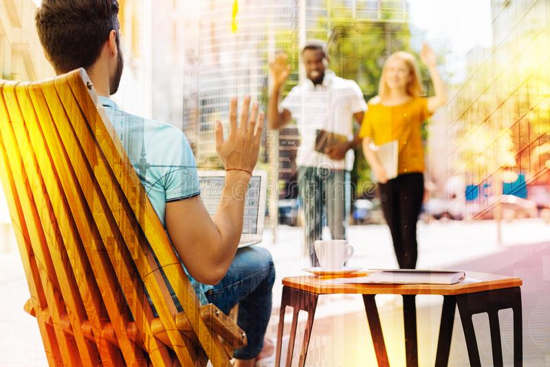 Young people waving when seeing their friend sitting in a cafe alone. Meeting friends. Cheerful emotional young people walking and waving their hands when stock photography
