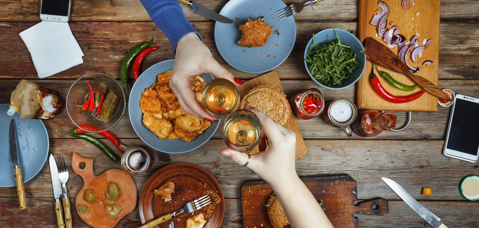 Meeting friends at the dinner table with American snacks and wine. Up of glasses of wine toast. stock photos