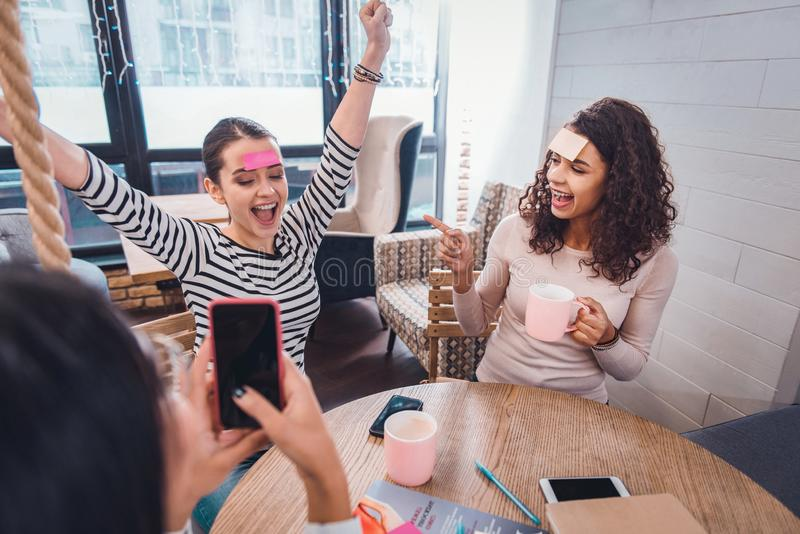 Happy positive nice women having fun together. Meeting of friends. Happy positive women having fun together while meeting in the cafe royalty free stock photography