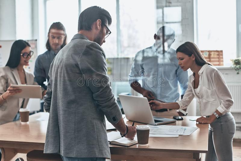Daily meeting. Group of young modern people working and communicating together while standing behind the glass wall in the board royalty free stock photography