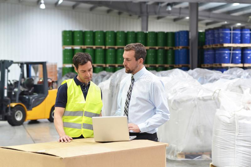 Meeting of the manager and worker in the warehouse - forklift an royalty free stock photos