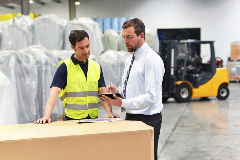 Meeting of the manager and worker in the warehouse - forklift an royalty free stock photo