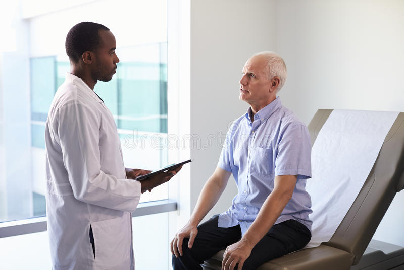 Meeting With Mature Male医生患者在检查屋子里 免版税库存照片