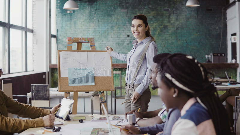 Meeting of mixed race business team. Woman manager presenting financial data to group of people at modern office. Female team leader using graphs and board royalty free stock image
